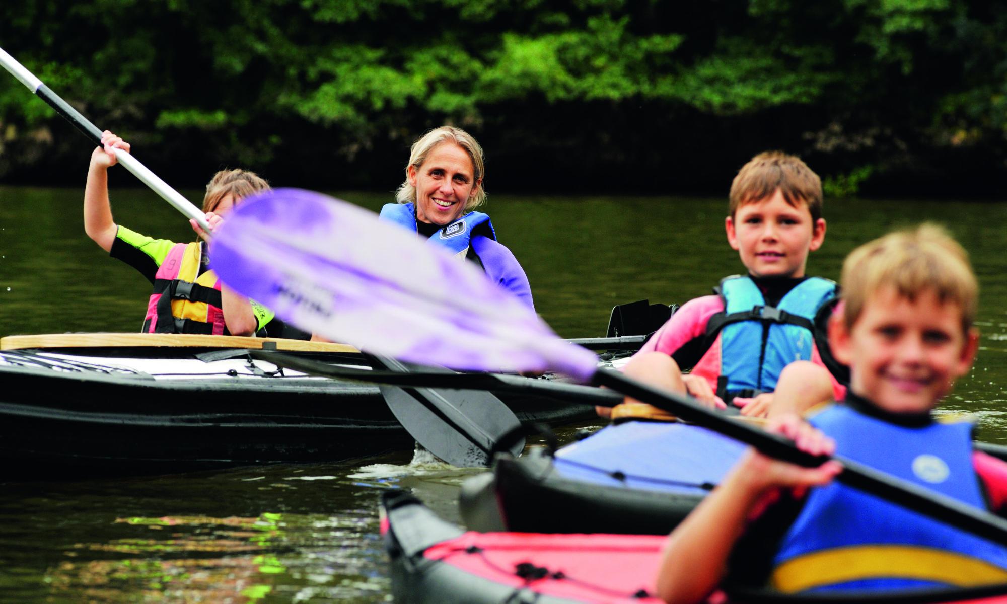 une maman avec ces enfants en famille en kayak pliants